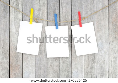 Three empty white photo frames hanging with clothespins on wooden background  - stock photo