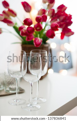 Three empty wine glasses on a table and a bouquet of flowers in daylight - stock photo