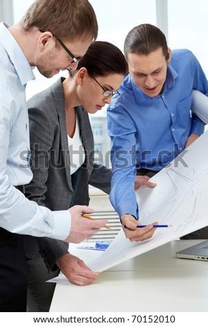 Three engineers examining a sketch of plane - stock photo