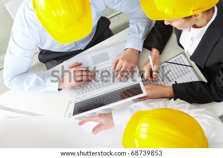 Three engineers in helmets working with a laptop