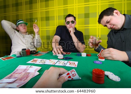 Three equal young men playing poker - stock photo