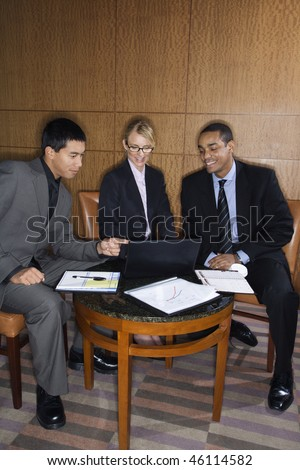 Three ethnically diverse business people sit at a small table and look at a laptop together. Vertical format. - stock photo