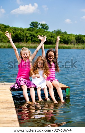 Three excited  girls sitting on the wooden bridge - stock photo