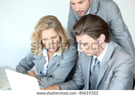 Three executives examining laptop computer