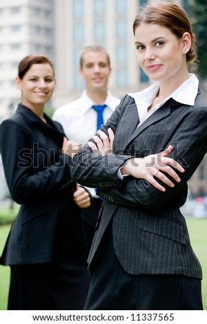 Three executives standing outside with city buildings behind - stock photo