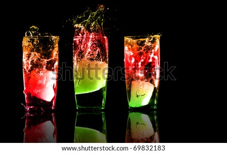Three exotic cocktails or juice with reflections on a black background - stock photo
