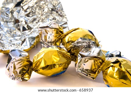 Three expensive gold and silver foil wrapped chocolates with a emptied wrapper in the background and room for text. - stock photo