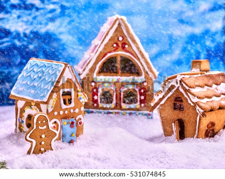 Three fabulous gingerbread house for Christmas. Gingerbread man winter background. Snowfall and Christmas.