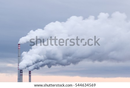Three factory chimneys smoking, heavy white smoke on the blue and orange sky.