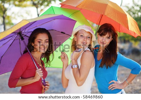 Three fashion teenage girls posing with colorful umbrellas in autumn park - stock photo