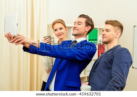Three fellow employees are doing selfie in the office. - stock photo