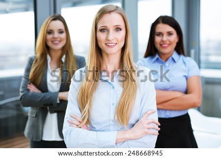 Three female business partners standing in an office and looking at the camera - stock photo