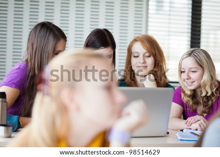 Three female college students working on their homework/having a chat in between the lectures (color toned image) - stock photo