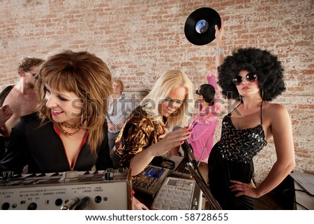 Three female DJs performing at a 1970s Disco Music Party - stock photo