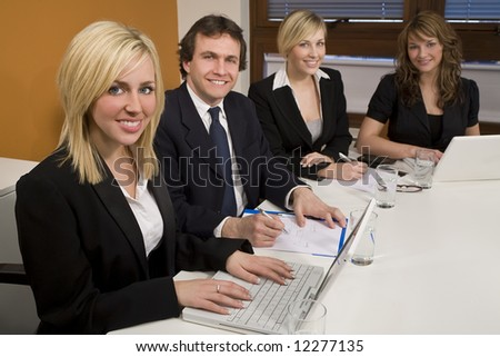 Three female executives and one male having a meeting in a boardroom - the focus is on the blond businesswoman in the foreground. - stock photo
