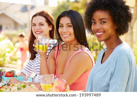 Three Female Friends Enjoying Meal At Outdoor Party - stock photo