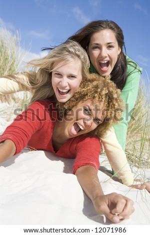 Three female friends having fun and laughing at beach - stock photo