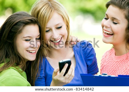 Three Female Friends Laughing and Looking at Cell Phone - stock photo
