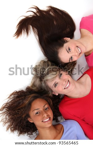 Three female friends laying next to each other - stock photo
