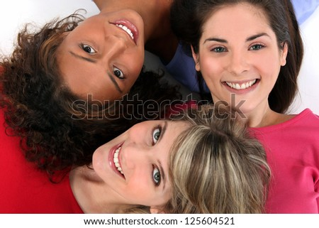 Three female friends laying together - stock photo