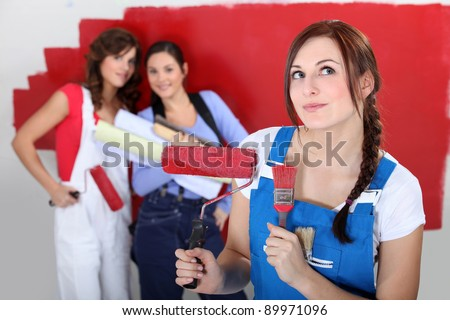 Three female friends painting wall - stock photo