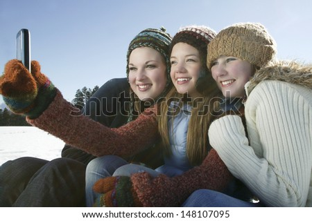 Three female friends taking self portrait through cell phone in winter - stock photo