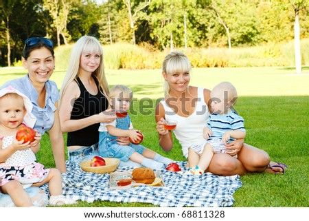 Three female friends with toddler children in the backyard - stock photo