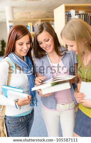 Three female high school student standing with books at library - stock photo