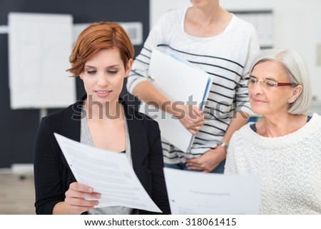 Three Female Office Workers Reading a Business Document Together Inside the Workplace.