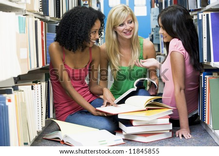 Three female students sitting on floor of library surrounded by books - stock photo