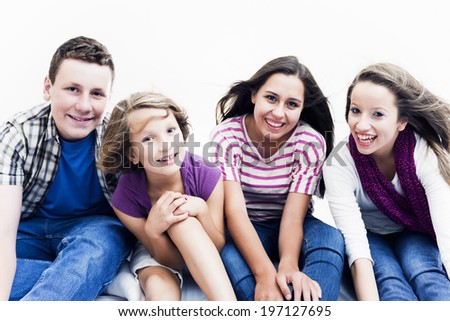 Three females and a male sitting beside each other and smiling. - stock photo