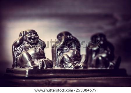 Three figures of Buddha philosophy on wooden background - stock photo