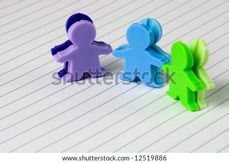 Three figurines of little men on a piece of writing paper