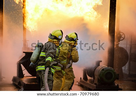 Three firefighters advance with a hose line. - stock photo