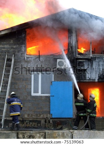 Three firefighters extinguish a fire in an apartment house - stock photo