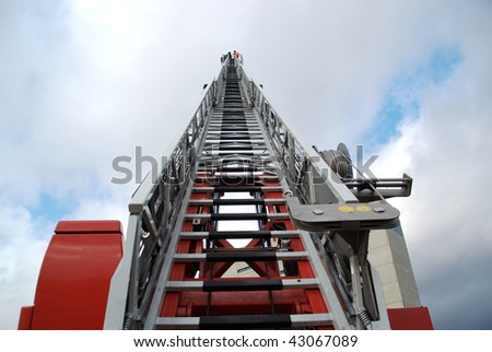 Three firefighters on a ladder of a fire truck. Photo taken from streetlevel. - stock photo