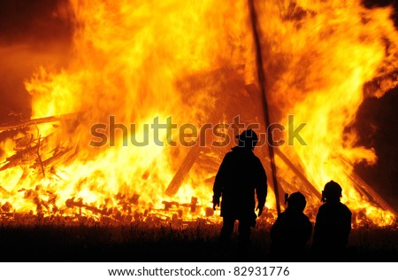 Three firefighters outlined against a massive blaze - stock photo