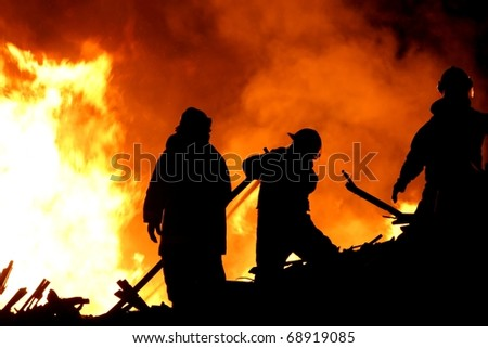 Three fireman in silhouette fighting a raging fire - stock photo