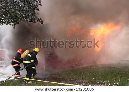 Three firemen during an intense training with a house in flame in the background - stock photo
