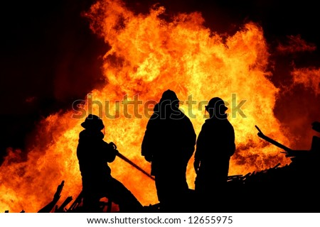 Three firemen fighting a raging fire with huge flames of burning scrap timber