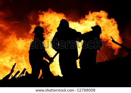 Three firemen fighting a raging fire with huge flames of burning scrap timber - stock photo