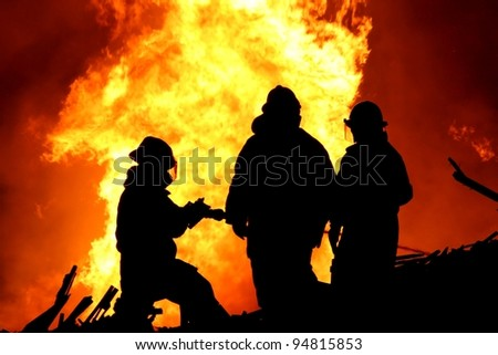Three firemen fighting a raging fire with huge flames of burning  timber - stock photo