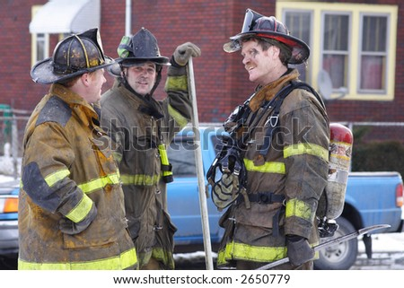 Three Firemen talking after putting out a fire