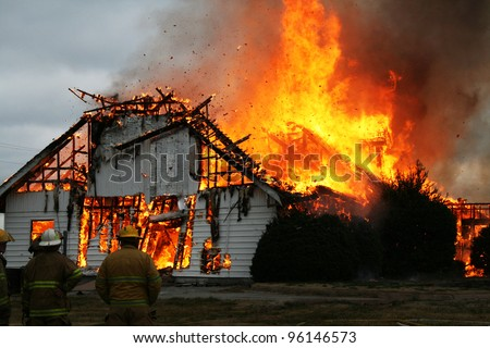 Three firemen watch an out of control blaze to assure the fire doesn't spread any further. - stock photo