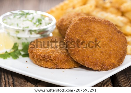 Three Fishburgers with French Fries on wooden background (close-up shot)