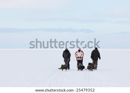 Three fishermans returning from their fishing places with fishing tackles on the sledges