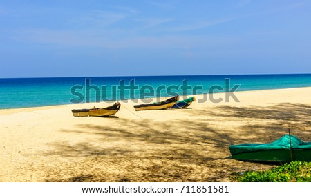 Three fishing boats tied by robes on the beach shades from the trees, under blue sky