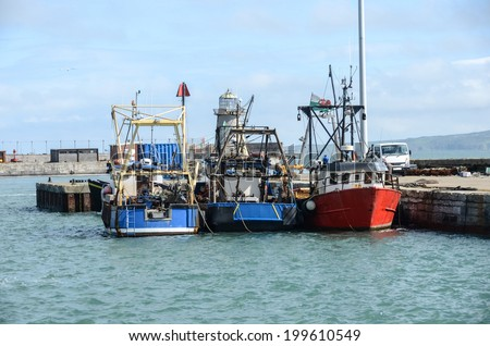 Three fishing boats tied up in harbour