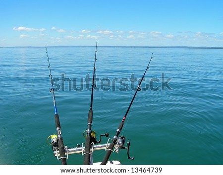 Three fishing rods cast into a blue calm sea.