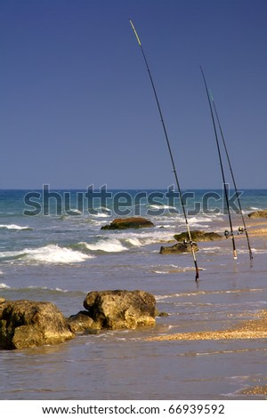 Three fishing rods on a rocky beach